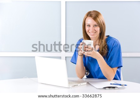 Female nurse at a desk working in a modern office - stock photo