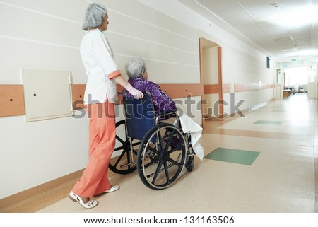 female nurse carer and aged elderly patient woman in wheelchair at clinic hallway - stock photo