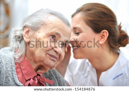Female nurse is speaking in senior woman ear - stock photo