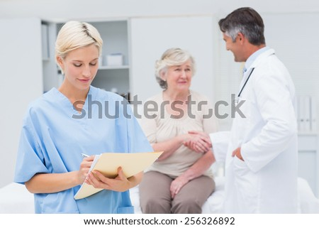 Female nurse making reports while doctor and patient shaking hands in background at clinic - stock photo