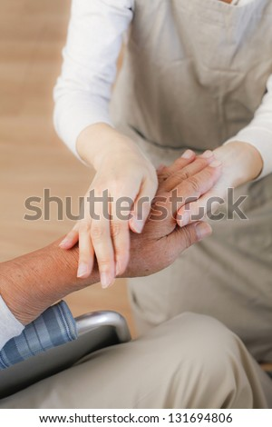 female nurse massaging arthritic hands of elderly man at retirement community center.