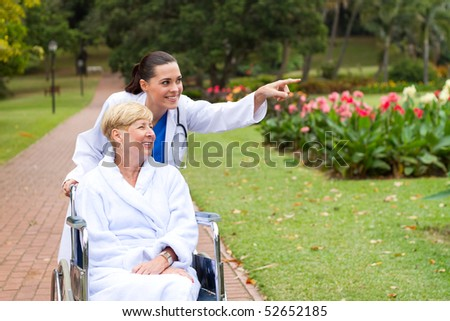 female nurse taking disabled senior patient for a walk outdoors