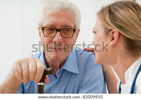 Female nurse talking and taking care of senior old man at hospital - stock photo