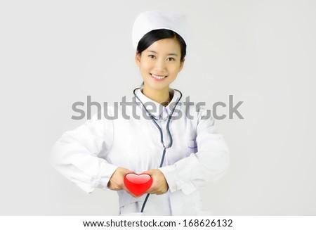 Female nurse with the stethoscope holding heart - stock photo