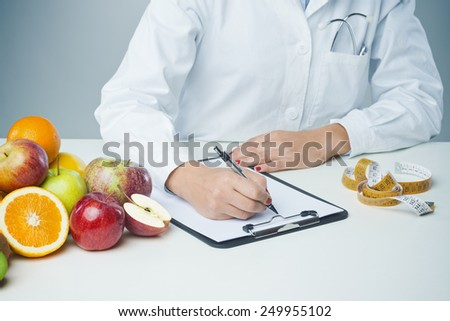 Female nutritionist at work writing documents on a clipboard with fresh fruit on foreground - stock photo