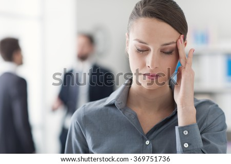 Female office worker having an headache, she has eyes closed and she is touching her temple, stress and health care concept