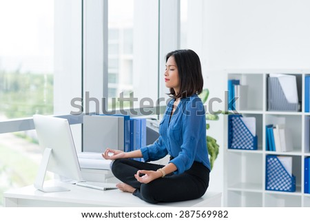 Female office worker in lotus position sitting on table - stock photo