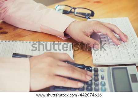 Female office worker typing on the keyboard and using a calculator to calculate the numbers vintage tone - stock photo