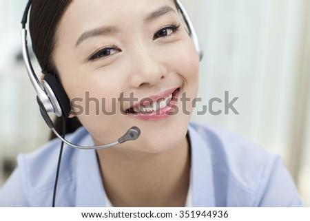 Female office worker wearing headset,portrait - stock photo