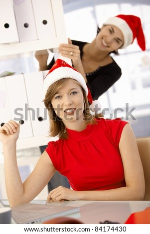 Female office workers having fun in office wearing Santa Claus hat.? - stock photo