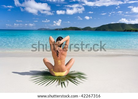 female on tropical beach sitting on green leaf relaxing in yellow bikini and tanning in caribbean