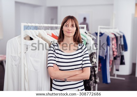 Female Owner of a Clothing Store Inside her Shop, Smiling at the Camera with Arms Crossing Over her Stomach. - stock photo