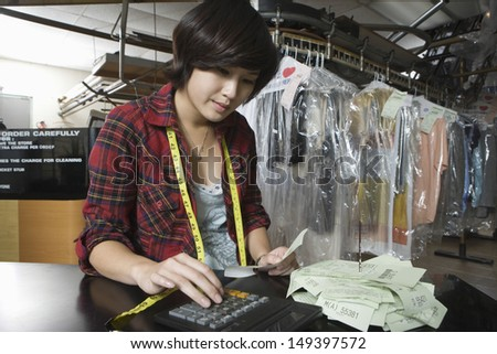 Female owner using calculator while holding bill in laundry - stock photo