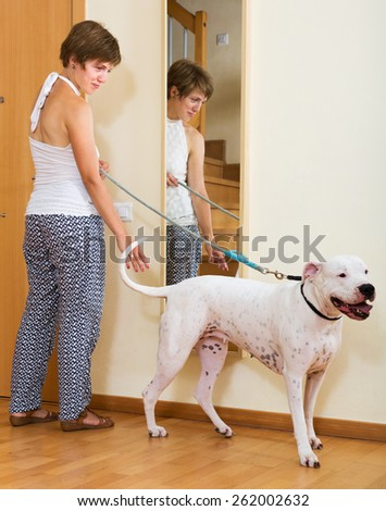Female owner with dogo Argentino on leash staying at door
