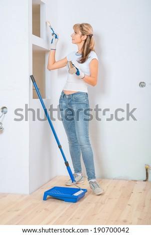 female painter painting white wall - stock photo