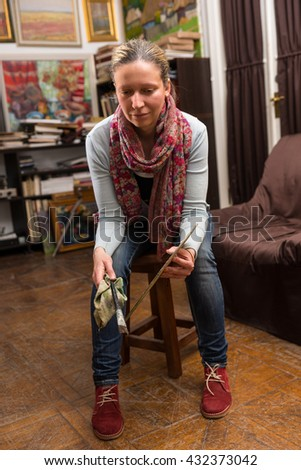 Female painter sitting painting in a studio or gallery holding a colorful artists palette and paintbrush in her hand - stock photo