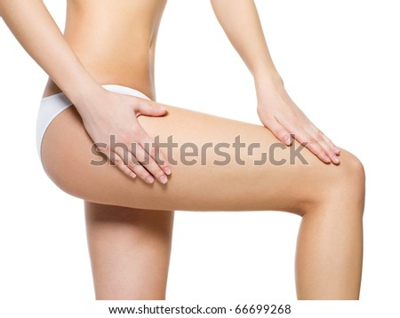 Female pampering cellulite skin on her legs - close-up shot on white background - stock photo