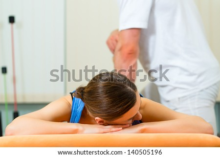 Female Patient at the physiotherapy doing physical exercises with her therapist, he gives her a medical massage - stock photo