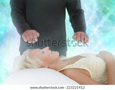 Female patient lying with eyes closed and male healer with hands hovering channeling energy with misty sparkling green energy field all around - stock photo