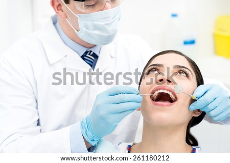Female patient undergoing a dental checkup - stock photo