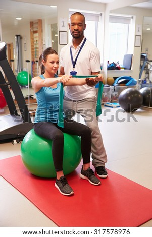 Female Patient Working With Physiotherapist In Hospital - stock photo