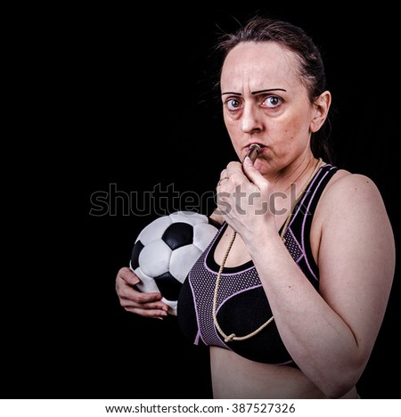 Female PE teacher in gym class. Holding soccer ball and blowing whistle. Black background with copy space. - stock photo