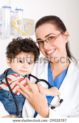 female pediatrician holding a cute baby boy - stock photo