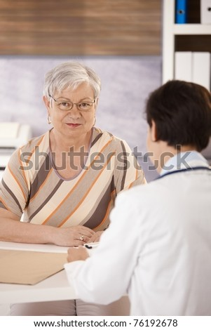 Female pensioner at doctors office looking at camera.? - stock photo