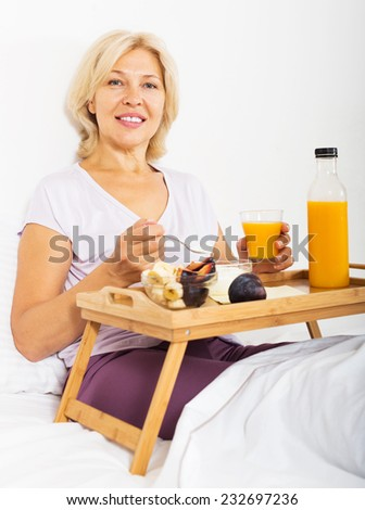 female pensioner with orange juice, berries and yogurt at overbed table