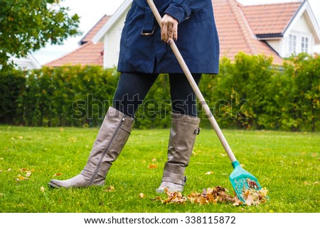Female person raking green grass from brown leaves at autumn in tall grey boots - stock photo