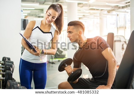 Female personal trainer showing exercise results to her male client in a gym.