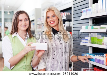 Female Pharmacist Advising Customer At Pharmacy In Front Of Shelves With Pharmaceuticals. - stock photo