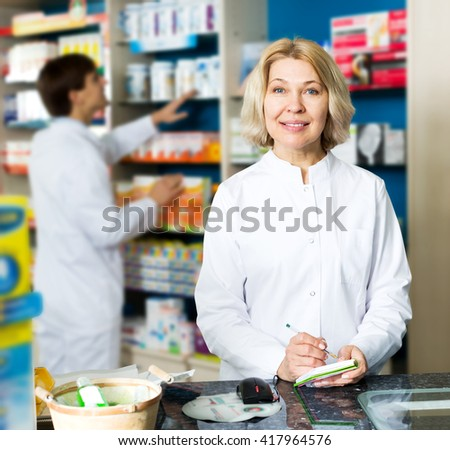 Female pharmacist and male pharmacy technician posing in pharmacy