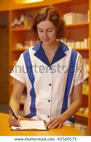Female pharmacist filling out questionnaire in pharmacy