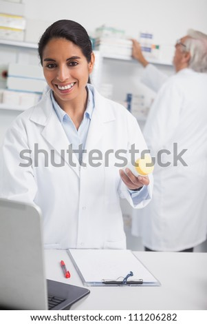 Female pharmacist holding a drug box while smiling in hospital ward