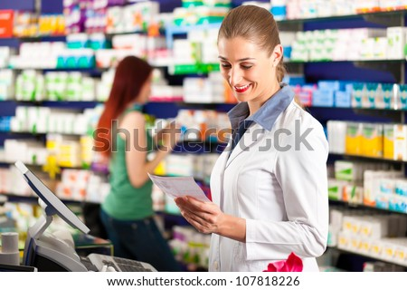 Female pharmacist in her pharmacy with a client - stock photo