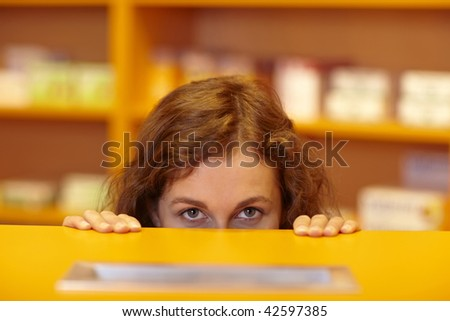 Female pharmacist looking up behind counter in pharmacy - stock photo