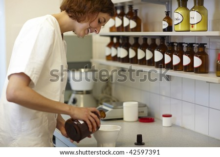 Female pharmacist mixing drug ingredients in lab - stock photo