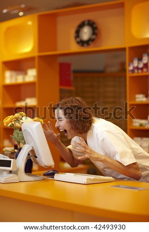 Female pharmacist screaming at computer on counter - stock photo