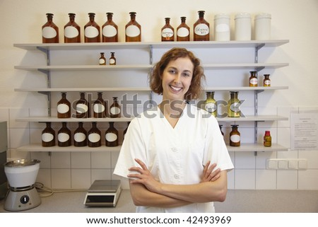 Female pharmacist standing in lab with shelf - stock photo