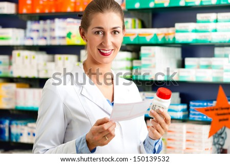 Female pharmacist standing in pharmacy with pharmaceuticals and a prescription slip - stock photo