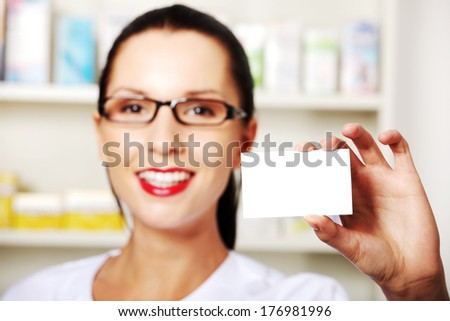Female pharmacist with business card in pharmacy, focus on card  - stock photo