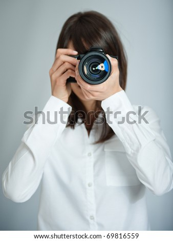 Female photographer aiming her camera at you - stock photo
