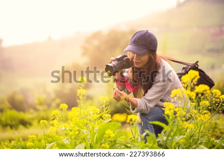 Female photographer at flower field - stock photo