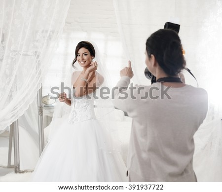 Female photographer photographing beautiful happy bride indoors. - stock photo