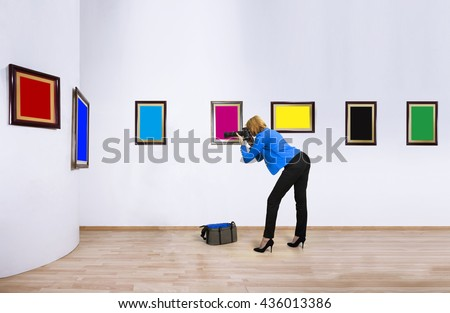 Female photographer, reporter, shooting at blank of CMYK and RGB color frames in art gallery. - stock photo