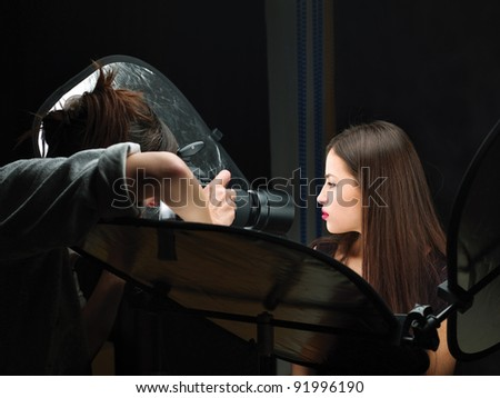 Female photographer shooting close up model's lips in studio