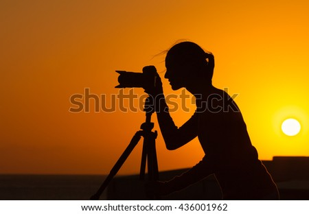 Female photographer taking photos outdoors.