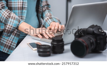 Female photographer working in her studio hands close up and digital camera on foreground - stock photo