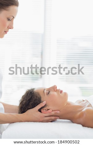 Female physical therapist massaging woman in health spa - stock photo